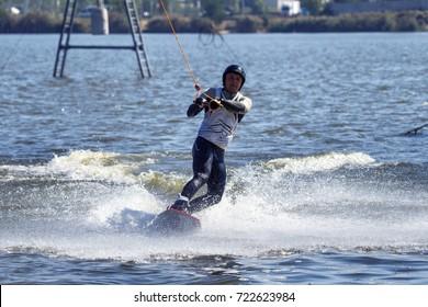 Wake Park. Summer beach water sports. Athlete glides on water on board. Kite on water. Kiteboarding, Wakeboarding. Athlete in water suit on blackboard. Summer sports background