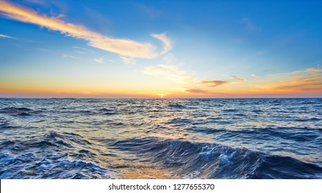 Wake of the ship in the sea against sunset and cloudy sky