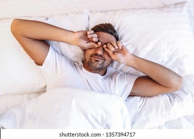 Wake up Sleepy. Dreams. Handsome man is rubbing his eyes while lying in a bed at home