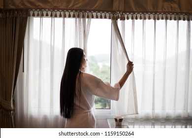 wake up :Woman in the morning holding a cup of tea or coffee and looking at the sunrise standing near the window in her home