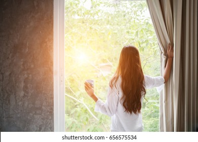 wake up :Woman in the morning holding a cup of tea or coffee and looking at the sunrise standing near the window in her home ,soft focus