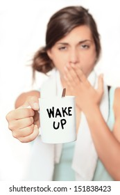 Wake up - young woman in the morning taking a coffee to help her get ready for the day - shallow depth and selective focus on cup