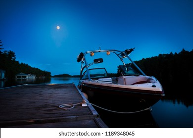 A wakeboard boat docked on Lake Joseph in the evening with the moon in the background