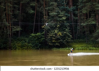Wakeboard. Man wakeboarding on lake in the forest. Active lifestyle. Extreme water sport.