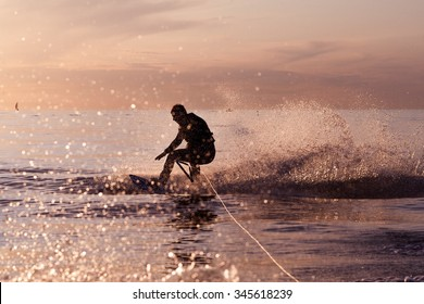 Wakeboard ride on tranquil waters at a sunset. Water splashing from the tow boat to a rookie wake boarder learning and loosing balance