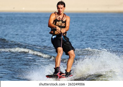 Wakeboarder in blackl shorts riding in sunset.