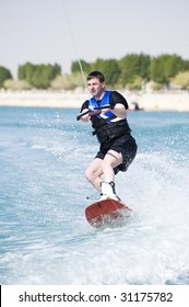 A wakeboarder enjoying the action of riding the wake of the boat.