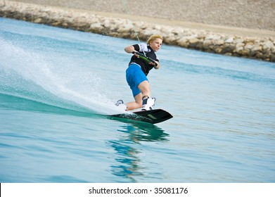 A wake-boarder enjoying the action of riding the wake of the boat.