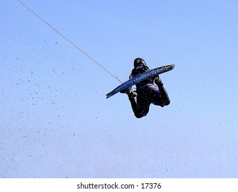Wakeboarder jumps against a blue sky