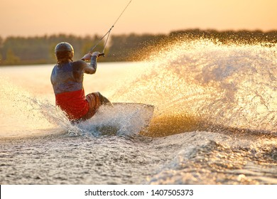 Wakeboarder making tricks. Low angle shot of man wakeboarding on a lake. Man water skiing at sunset.