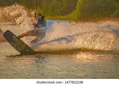 Wakeboarder making tricks. Low angle shot of man wakeboarding on a lake. Man water skiing at sunset.