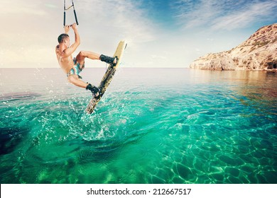 Wakeboarder making tricks on the sea. Wakeboarding. Water sports on the beach.