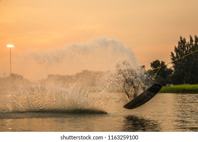 Wakeboarder making tricks at sunset, Bangkok, Thailand