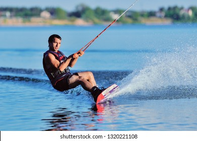 Wakeboarder surfing across a lake