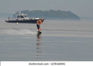 Wakeboarder wakeboarding past a lobster boat in Casco Bay.