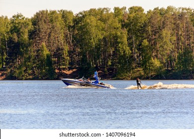 wakeboarding championship. woman in wetsuit riding wakeboard on wave of motorboat in summer lake. Unidentified wakeboarder participates. Silhouette of wake skater. he launches off wake. Moscow 05/2019