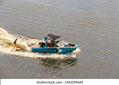 wakeboarding championship. woman in wetsuit riding wakeboard on wave of motorboat in summer lake. Unidentified wakeboarder participates. Silhouette of wake skater. he launches off wake. Moscow 07/2019