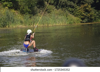 Wakeboarding is an extreme sport. Sports and recreation. Wakeboard electric traction. Cable wakeboarding. The athlete holds on to the halyard and performs various tricks.