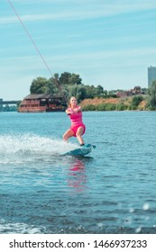 Wakeboarding lesson. Fit attractive wakeboarder looking straight ahead while riding over the surface of water