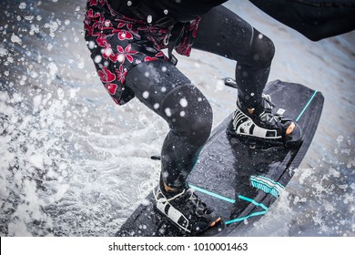wakeboarding man in a splash of water, legs only