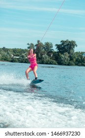 Wakeboarding rope. Vertical shot of a blonde girl sliding over the surface of water on a wakeboard using the rope handle
