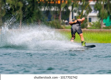 Wakeboarding sportsman jumping high wake boarding relay trick with huge water splash in the cable park is active sports life style recreation hobby fun of young new generation