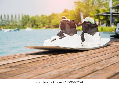 Wakeboarding of X-Stream athletes after completing the race, placed on a wooden floor with a beautiful lake background, with copy space and decorating websites or text input.