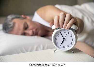 Waked Up. Hand turns off the alarm clock waking up at morning . soft skin tone . Exhausted man being awakened by an alarm clock in his bedroom