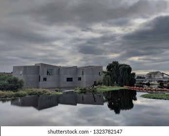 WAKEFIELD, ENGLAND - SEPTEMBER 2, 2018: Beyond a weir, exterior of striking, brutalist, concrete Hepworth Gallery in Wakefield, UK, named for the sculptor Barbara Hepworth who was born in the town