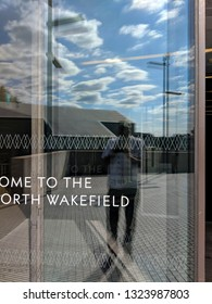 WAKEFIELD, ENGLAND - SEPTEMBER 2, 2018: Sign, a man and bright blue cloudy sky reflected in the windows of the striking, brutalist, concrete Hepworth Gallery in Wakefield, Yorkshire, UK