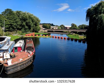 WAKEFIELD, ENGLAND - SEPTEMBER 2, 2018: Barges and an orange barrage protecting boats from a weir, Wakefield, UK