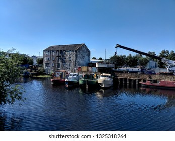 WAKEFIELD, ENGLAND - SEPTEMBER 2, 2018: Barges and boats moored on a wharf in front of an old warehouse, Wakefield, UK