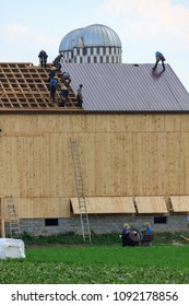 "Wakefield, PA, USA - June 24. 2010: Called a ""barn raising"", Amish farmers construct a barn in a day in Lancaster County."