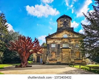WAKEFIELD, YORKSHIRE, UK - APRIL 13, 2019:  Iron Tree by Al Weiwei and St Bartholomew's Chapel , 1774, in the grounds of Yorkshire Sculpture Park, near Wakefield, West Yorkshire, UK