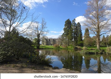 Wakehurst Place, Haywards Heath / UK - May 25, 2012: A scenic view of the pond, with reflection of large trees and conifers, on a beautiful spring day with blue sky