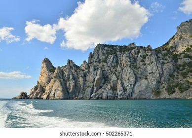 Wakes from boats on the backdrop of the cliffs. Crimea.