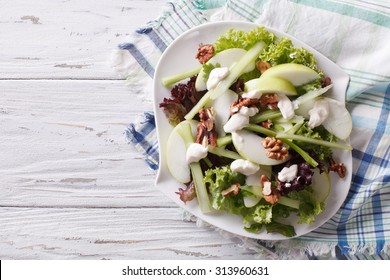 Waldorf Salad with apples, celery and walnuts on a plate. horizontal view from above