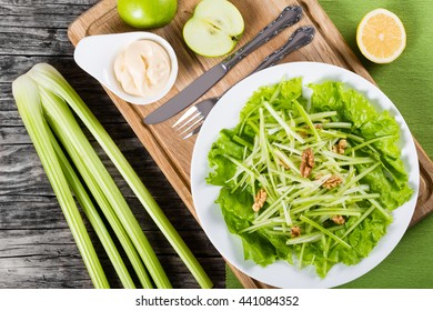 Waldorf Salad with green apples, celery and walnuts on a white dish, on a cutting board, classic recipe, view from above