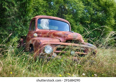 WALDRON, USA - JUNE 18, 2015: A frontal view of an old International Harvester truck that is slowly rusting on a farm on Waldron Island shows the front grill, hood, and insignia on the grille.