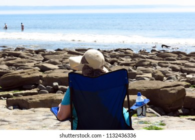 Wales, United Kingdom - June 1 2018: Relaxed elderly woman sitting in a chair on the beach looking at the ocean