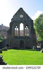 Wales, vale of Llangollen. The Cistercian Abbey of Valle Crucis. A view to the west front part of the complex, with the wall silhouetted against the bright spring sun.