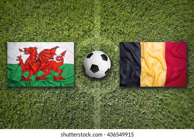 Wales vs. Belgium flags on green soccer field