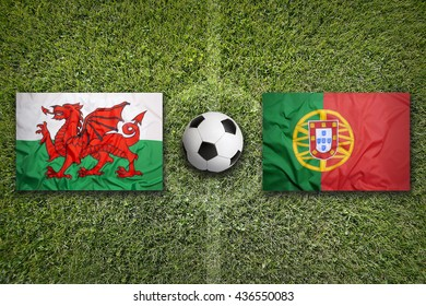 Wales vs. Portugal flags on green soccer field