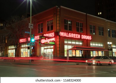 Walgreen Drugs drugstore located at the corner of E. Houston and Navarro Streets with streaming lights of a car passing by - San Antonio, TX, USA - February 17, 2018