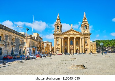 The walk along the capstones of old Fosos (granaries) square with a view on scenic St Publius Parish chrurch, Floriana, Malta.