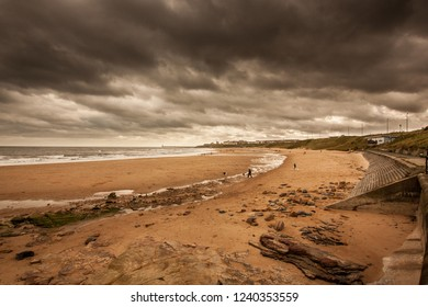 A walk along the coastline of Tynemouth Longsands at Cullercoats Bay near Newcastle, UK.