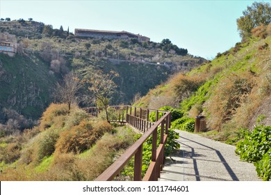 Walk along the footbridges of the Tagus River, In the background the National Tourism Parador of Toledo, path of the coastal edge of the cliffs of the Tagus in the city of Toledo, Spain.