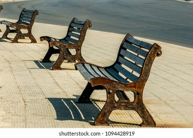 Walk along the seafront of Bari during the afternoon. Old benches, made of wood and iron, on the street.