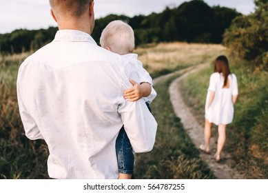 Walk of beautiful young family in white clothes with a young son blond in mountainous areas with tall grass at sunset. Dad keeps his son in his arms