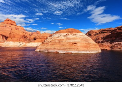Walk by tourist motor ship on water on sunset. The lake is surrounded with amazing coast from orange sandstone. Picturesque artificial huge reservoir Powell on the river Colorado, USA